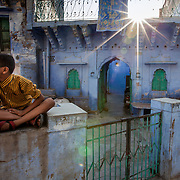 A young boys sits on his gate waiting.