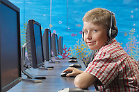 School boy wearing headphones in computer room, portrait