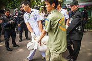"20 MAY 2010 - BANGKOK, THAILAND: Medical workers and forensics experts carry the body an of an anti government protester killed in Wat Pathumwanaram near the Ratchaprasong Intersection in Bangkok past a Bangkok police SWAT team Thursday. At least some of the nine were so called ""Black Shirts"" armed fighters who support the Red Shirts. The day after a military crackdown killed at least six people, Thai authorities continued mopping up operations around the site of the Red Shirt rally stage and battle fires set by Red Shirt supporters in the luxury malls around the intersection. They also recovered at least seven bodies from Wat Pathumwanaram, next to Central World mall, which was destroyed by fire. The nine people killed in the temple were not included in the government's body count from Wednesday.    PHOTO BY JACK KURTZ"