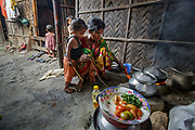 Adult woman in urban slum in Bangladesh cooking over a traditional wood burning stove.