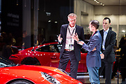 New York, NY - 12 April 2017. Andreas Prueninger, the head of the GT line of cars at Porsche, giving an interview. A new Porsche 911 GT3 is in the foreground.