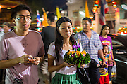 28 NOVEMBER 2012 - BANGKOK, THAILAND:  A couple walks into Wat Yannawa with their krathongs on Loy Krathong in Bangkok. Loy Krathong takes place on the evening of the full moon of the 12th month in the traditional Thai lunar calendar. In the western calendar this usually falls in November. Loy means 'to float', while krathong refers to the usually lotus-shaped container which floats on the water. Traditional krathongs are made of the layers of the trunk of a banana tree or a spider lily plant. Now, many people use krathongs of baked bread which disintegrate in the water and feed the fish. A krathong is decorated with elaborately folded banana leaves, incense sticks, and a candle. A small coin is sometimes included as an offering to the river spirits. On the night of the full moon, Thais launch their krathong on a river, canal or a pond, making a wish as they do so.   PHOTO BY JACK KURTZ