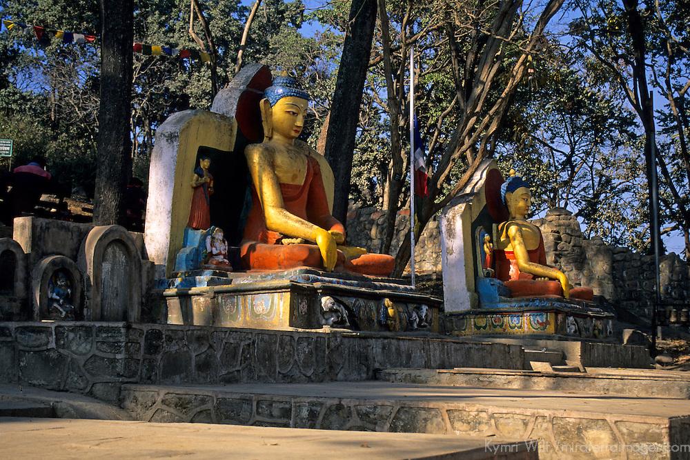 Asia, Nepal, Kathmandu. Sitting Buddhas at entrance to Swayambhunath Stupa.