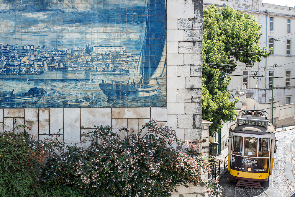 Tram28 passes on Rue Limoeiro next to an azulejo in Largo Santa Luzia.