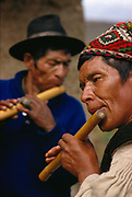 Quechua Indians playing flute at village festival in the Andes in Bolivia.