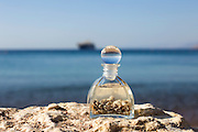 A bottle with seashells on the beach selective focus on the foreground