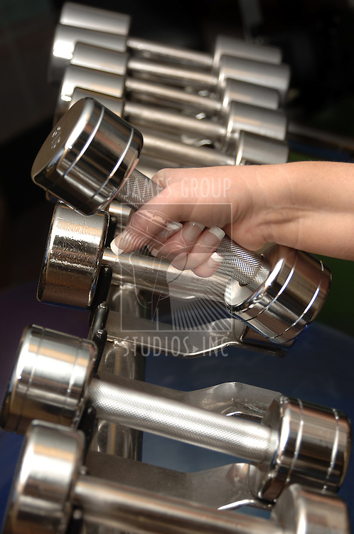 Female hand grabbing a dumbbell from a rack of free weights