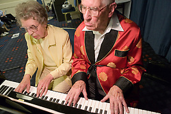Elderly couple playing piano,