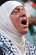 During a vigil held in Montreal in solidarity with the people of Gaza, a woman screams his pain for those who have been killed by Israeli attacks.
