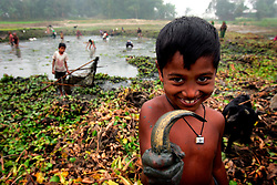 BANGLADESH SIRAJGANJ RADHUNIBARI 31JAN07 - A young boy displays his catch during a village pond fishing session in the countryside near the Jamuna river, an area traditionally prone to flooding during the Monsoon season.<br /> 