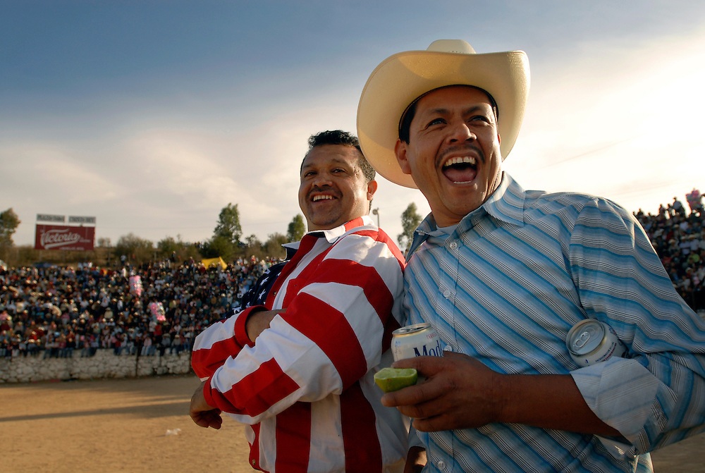 Juan Rodriguez, 42, (at left) wears a stars and stripes shirt to the norteño fiesta in Lagunillas, Mexico. Rodriguez and Medardo Dominguez, Jr., 37, both of whom are Wallingford steel workers, enjoy centerstage at the bullring in December 2006. The norteños pool their steel mill earnings during the year and throw an all-day block party for their beloved village every December.