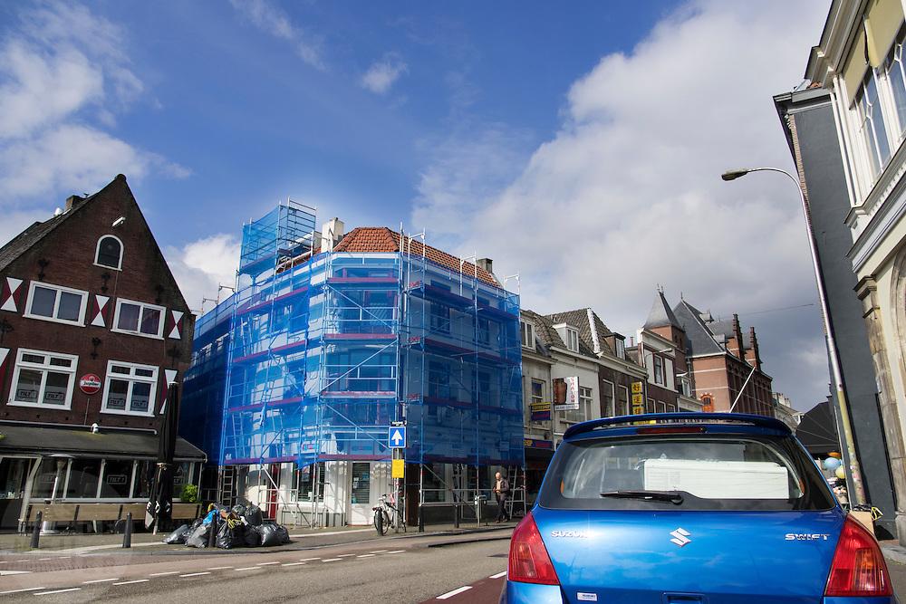 In Utrecht staat een blauwe auto geparkeerd vlakbij een blauwe steiger.<br /> <br /> In Utrecht a blue car is parked next to blue scaffold.