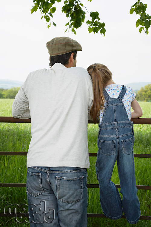 Father and daughter (5-6) standing at fence in countryside