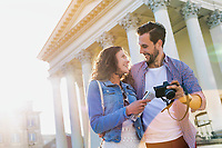 Portrait of handsome young man showing pictures on camera to his beautiful girlfriend while standing against museum with lens flare in background