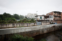 Gioia Tauro, Italy - 1 September, 2012: A man walks by the river and an unfinished home in Gioia Tauro, Italy, a mafia stronghold on September 1st, 2012.  The unfinished concrete buildings, which are very common throughout Calabria, are the result of the inability to go beyond the merely useful, creating functionality without regard for form.<br /> <br /> The current mayor of Gioia Tauro, Renato Bellofiore, was elected in 2010 after the former mayor and deputy mayor, Giorgio Dal Torrione and Rosario Schiavone, were arrested on Mafia charges in 2008. Both had been forced to step down when the city council was dissolved on suspicion of Mafia infiltration. Gioia Tauro is a city of 19,000 people built on an ancient Greek necrapolis and that today has the largest seaport in Italy and the sevent largest container port in Europe with its extension of 4,646 meters. Because the port is not connected to adeguate roads or rails, the ships mostly transfer containers to smaller vessels and little economic activity stays local. To authorities, the port is best known as the first point of entry for most of the cocaine that enters Europe from South America. In a routine rais earlier this month, authorities seized 176 kilos of pure cocaine with an estimated street value of 38 million euros.<br /> <br /> Calabria is one of the poorest Italian regions which suffers from lack of basic services (hospitals without proper equipment, irregular electricity and water), the product of disparate political interests vying for power. The region is dominated by the 'Ndrangheta (pronounced en-Drang-get-A), which authorities say is the most powerful in Italy because it is the welthiest and best organized.<br /> <br /> The region today has nearly 20 percent unemployment, 40 percent youth unemployment and among the lowest female unemployment and broadband Internet levels in Italy. Business suffer since poor infrastructure drives up transport costs.<br /> <br /> Last summer the European Union's anti-fraud office demanded that Italy redirect 380 mil
