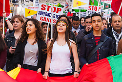 London, October 19th 2014. Hundreds of London's Kurdish community march throgh the capital in protest against ISIS and the Turkish government who they accuse, by not getting involved in military action against ISIS, of using the Jihadists to wipe out Kurds who have long been campaigning for an independent Kurdistan. PICTURED: Protesters help carry a giant Kurdish flag.