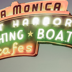"Santa Monica Pier sign vintage panoramic photo.  Panorama picture ratio is 1:3. The famous Santa Monica Pier sign says ""Santa Monica Yacht Harbor Sport Fishing Boating Cafes"". Santa Monica Pier is a landmark located in Los Angeles County Southern California and has an amusement park with a ferris wheel, roller coaster, restaurants, and other attractions. Photo has vintage 1960's tone."
