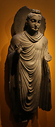 The Buddha Gandhara, about AD200.  Schist.  In a classic standing pose, the Buddha raises his right hand in the fear-dispelling gesture; his left hand would have held the folds of his monk's robe.  The finery carved head and the modelling of the robe show Greco-Roman influences.
