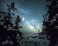 A lone figure stands under an expanse of stars, casting a beam from his headlamp towards the milky way.