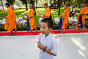 20 OCTOBER 2012 - BANGKOK, THAILAND:  A boy prays as Buddhist monks pass him at a special alms giving ceremony in Bangkok. More than 2,600 Buddhist Monks from across Bangkok and thousands of devout Thai Buddhists attended the mass alms giving ceremony in Benjasiri Park in Bangkok Saturday morning. The ceremony was to raise food and cash donations for Buddhist temples in Thailand's violence plagued southern provinces. Because of an ongoing long running insurgency by Muslim separatists many Buddhist monks in Pattani, Narathiwat and Yala, Thailand's three Muslim majority provinces, can't leave their temples without military escorts. Monks have been targeted by Muslim extremists because, in the view of the extremists, they represent the Thai state.       PHOTO BY JACK KURTZ