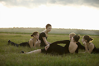 Young dancers lie in a field talking