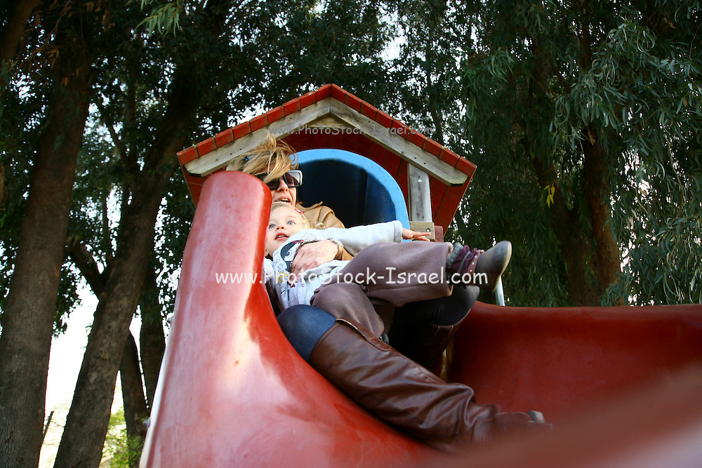 Female toddler of two and her grandmother are playing together on a slide in a public playground