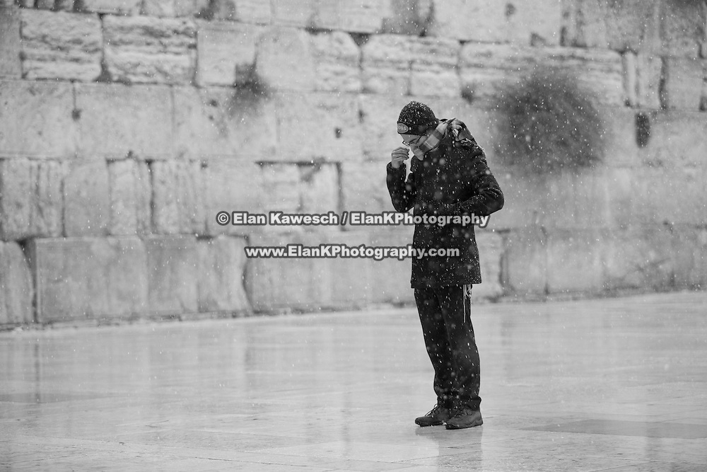 A man covers his face as snow and rain fall at The Western Wall on January 7, 2015 in Jerusalem, Israel. (Photo by Elan Kawesch)