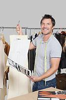 Portrait of male dressmaker holding sewing pattern, sketch and design draft