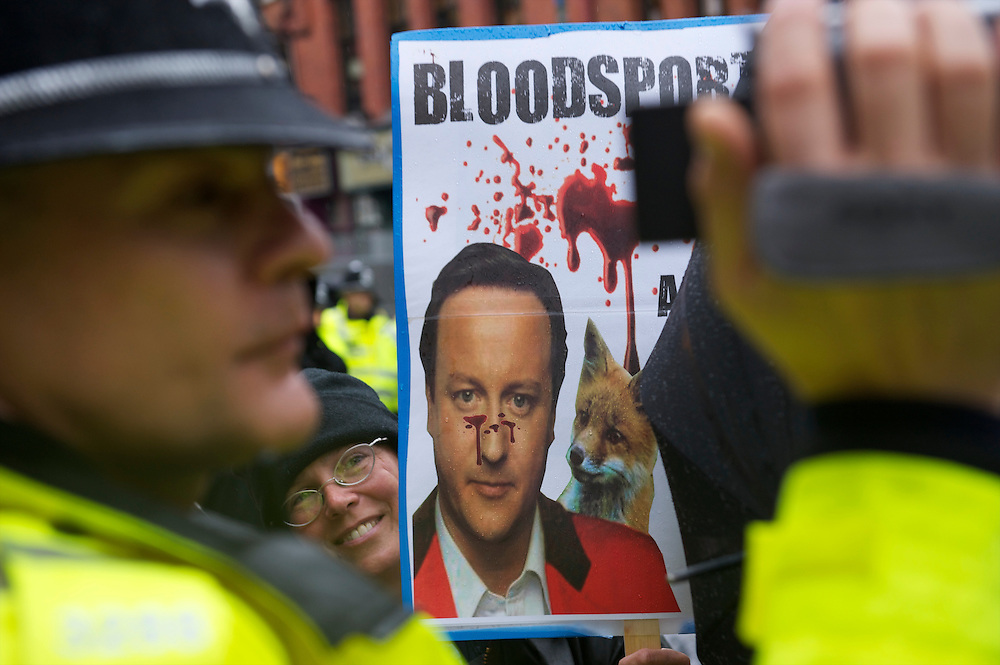 A policeman videotapes the activity of protestors who marched the streets of Birmingham to voice their opposition of Prime Minister David Cameron and the Conservatives on the first day of party conference at the ICC, Birmingham, UK on October 3, 2010.  This is the first conference since the government coalition with the Liberal Democrats.