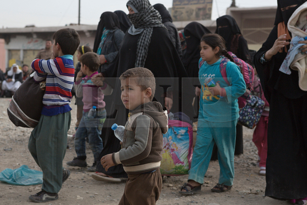 Licensed to London News Pictures. 10/11/2016. Mosul, Iraq. Women and children, escaping from areas within Mosul where fighting between Iraqi Security Forces and Islamic State militants are fighting, stand in line as they wait to board a bus in the city's Gogjali District. The bus, provided by the Iraqi Army, will take them to the safety of a refugee camp in Iraqi-Kurdistan.<br /> <br /> The battle to retake Mosul, which fell June 2014, started on the 16th of October 2016 with Iraqi Security Forces eventually reaching the city on the 1st of November. Since then elements of the Iraq Army and Police have succeeded in pushing into the city and retaking several neighbourhoods allowing civilians living there to be evacuated - though many more remain trapped within Mosul. Photo credit: Matt Cetti-Roberts/LNP