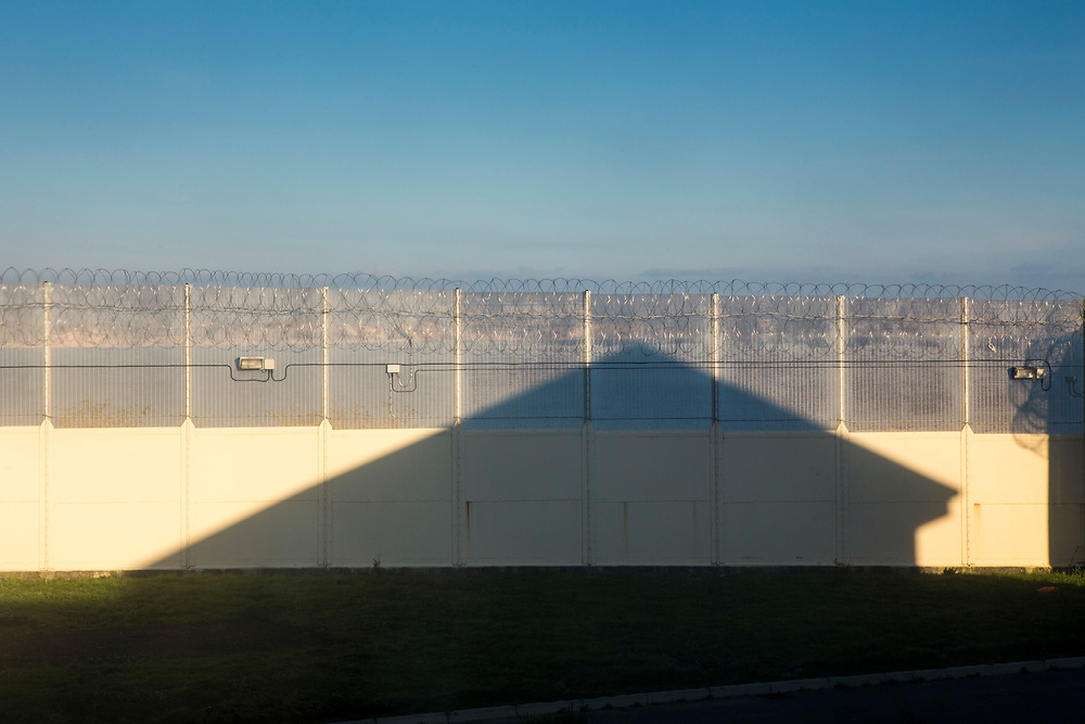 building shadow on the security fence inside HMP/YOI Portland, a resettlement prison with a capacity for 530 prisoners. Dorset, United Kingdom.