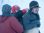 Trail sweeps Lisa Rhoades (center) and Carolyn Craig (left) adjust a bandage on Rick Swenson before he left for Rohn.