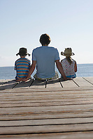 Father and two children (7-9) sitting on jetty back view