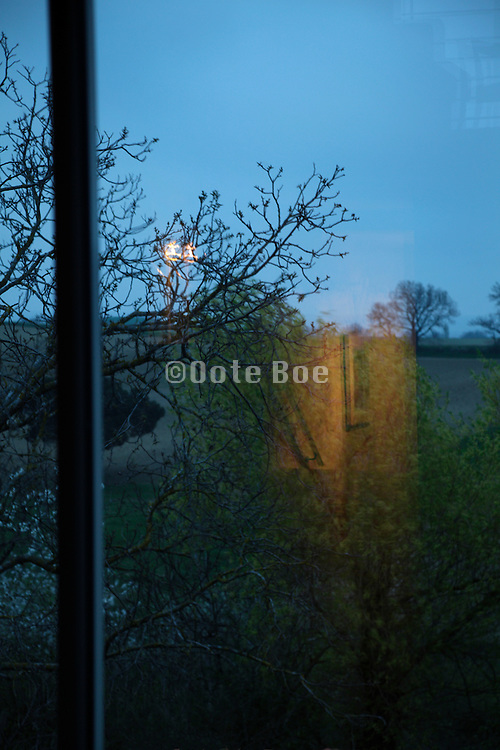 reflection from light from inside with trees and rural landscape