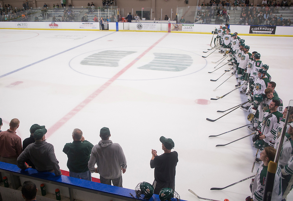 Alumni from the 1960s hockey team line up on the ice with the current team after the first period of the OU vs. Kent State hockey game in Bird Arena on September 30, 2016.