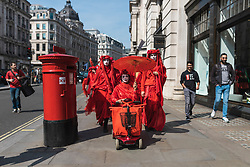© Licensed to London News Pictures. 15/04/2019. London, UK. Environmental activists from the Extinction Rebellion movement in fancy dress as they march down Regent Street during a series of direct actions taking place across the capital. The protests demand urgent action from governments on climate change. Photo credit: Rob Pinney/LNP