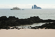 View from the beach of San Cristobal at Cerro Brujo towards Kicker Rock. The ship is M/S Tip Top III belonging to Galapagos Travel.