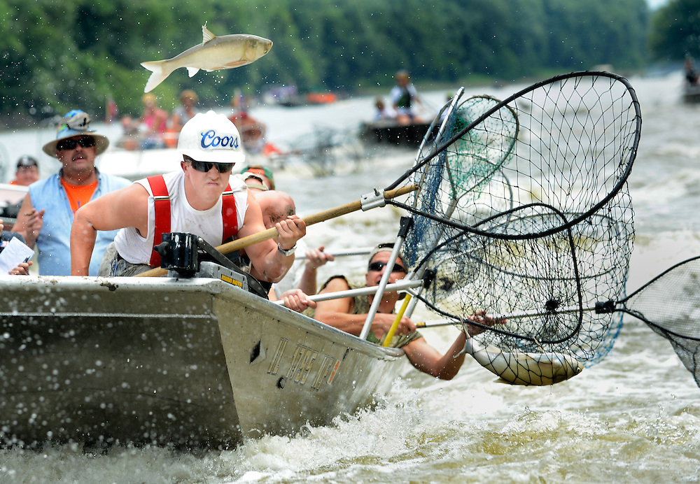 Nick Baker, of West Peoria, takes aim at a leaping Asian carp Friday in the lead position of a boat load of Peorians in the Redneck Fishing Derby in Bath. Hundred of people were on hand Friday for the opening of the event in which participants try to catch Asian carp in the air with nets.