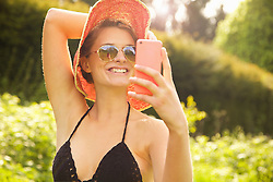 Smiling Young Woman Taking Selfie Outdoors