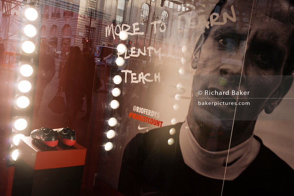 England footballer Rio Ferdinand features in a Nike ad whose face and boots are lit by bright lights in Lillywhites window.