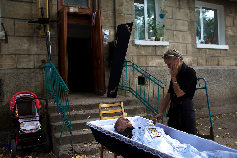 Dumitru Stuplaov was an ex-prisoner who died of MDR-TB.  His mother, Evgenia Stupalov, stands over his body at a wake. ..