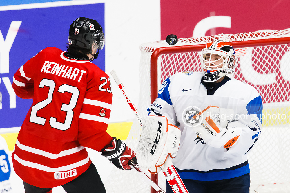 140104 Ishockey, JVM, Semifinal,  Kanada - Finland<br /> Icehockey, Junior World Cup, SF, Canada - Finland.<br /> Sam Reinhart, (CAN) and Juuse Saros, (FIN) focused on the puck.<br /> Endast f&ouml;r redaktionellt bruk.<br /> Editorial use only.<br /> &copy; Daniel Malmberg/Jkpg sports photo
