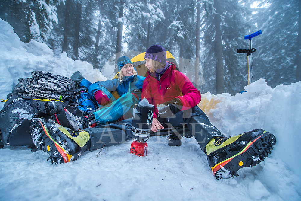 Two female mountaineers, as seen preparing a warm beverage, on a cold Winter day in the forests of Courmayeur, Italy.