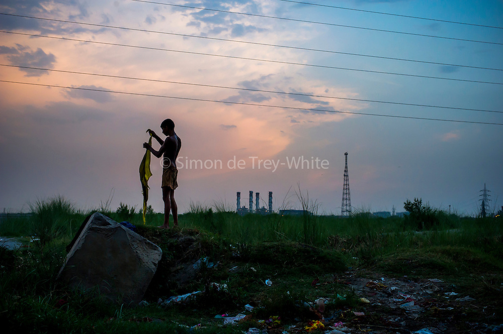 25th May 2014, Yamuna River, New Delhi, India. An elephant handler folds his clothes on a small island in the Yamuna river in New Delhi, India on the 25th May 2014<br /> <br /> Elephant handlers (Mahouts) eke out a living in makeshift camps on the banks of the Yamuna River in New Delhi. They survive on a small retainer paid by the elephant owners and by giving rides to passers by. The owners keep all the money from hiring the animals out for religious festivals, events and weddings, they also are involved in the illegal trade of captive elephants.The living conditions and treatment of elephants kept in cities in North India is extremely harsh, the handlers use the banned 'ankush' or bullhook to control the animals through daily beatings, the animals have no proper shelters are forced to walk on burning hot tarmac and stand for hours with their feet chained together. <br /> <br /> PHOTOGRAPH BY AND COPYRIGHT OF SIMON DE TREY-WHITE<br /> + 91 98103 99809<br /> email: simon@simondetreywhite.com photographer in delhi