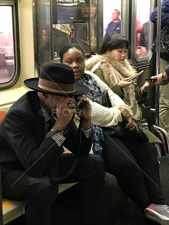 African American man on a New York City train taking photographs of the passengers