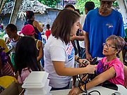29 JANUARY 2018 - SANTO DOMINGO, ALBAY, PHILIPPINES: A woman who lives on Mayon volcano and has been evacuated to a shelter in Santo Domingo gets her blood pressure checked during a wellness check at the shelter. Mayon volcano's eruptions continued Monday. At last count, more 80,000 people have been evacuated from their homes of the slopes of the volcano and are crowded into shelters in communities outside of the danger zone.    PHOTO BY JACK KURTZ