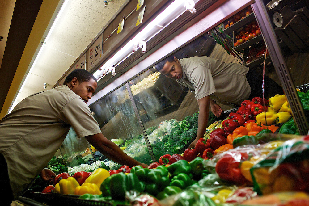 Elio Perdomo, restocks vegetables in the produce section at a Safeway grocery store in Silver Sping, MD. Perdomo, a student at Montgomery College, tries to take classes in the morning and works up to 16 hours a week at the supermarket.