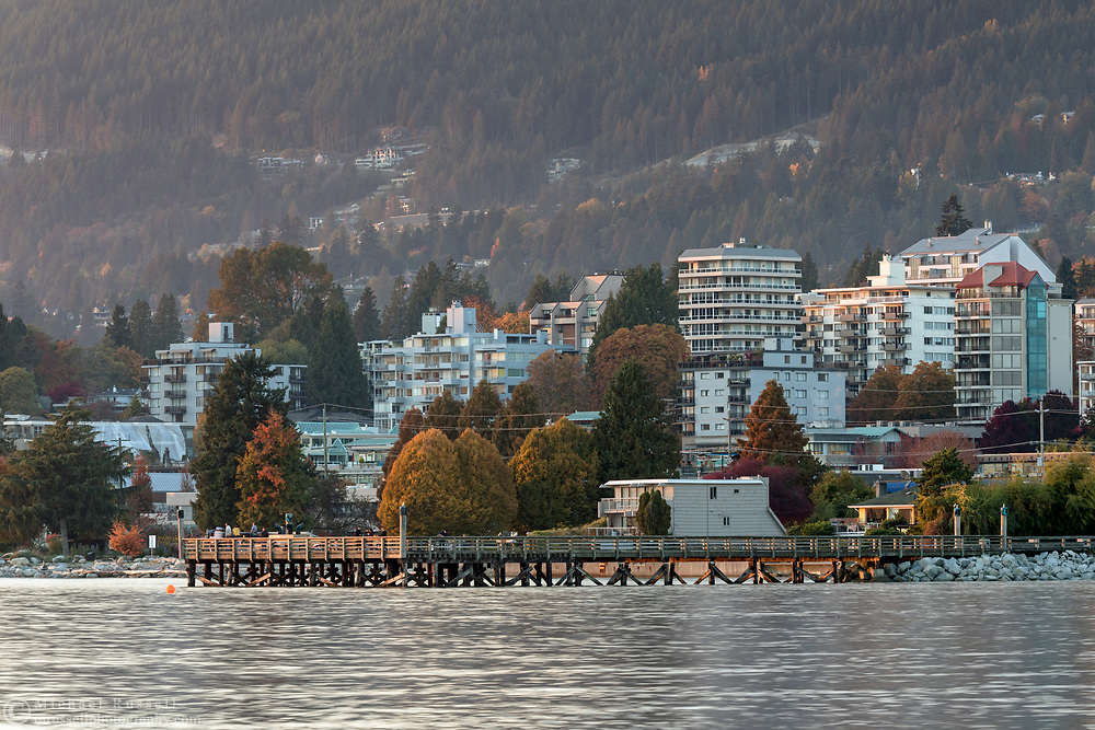 View of Ambleside Pier and West Vancouver during a fall sunset.  Photographed from Ambleside Beach in West Vancouver, British Columbia, Canada.