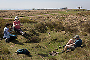 Walking friends rest and one puts socks back on after cooling his feet on a warm day at Rowberrow on Burrington Combe, 20th April 2019 near Langford, North Somerset, England.