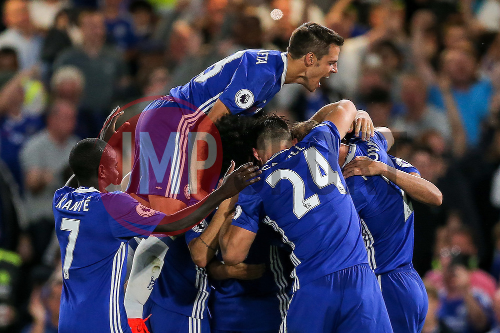 Cesar Azpilicueta of Chelsea jumps up as Eden Hazard of Chelsea celebrates scoring a goal from the penalty spot to make it 1-0 - Rogan Thomson/JMP - 15/08/2016 - FOOTBALL - Stamford Bridge Stadium - London, England - Chelsea v West Ham United - Premier League Opening Weekend.